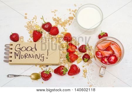 Good morning note in a notebook with craft brown pages ripe strawberries milk and oat muesli for breakfast