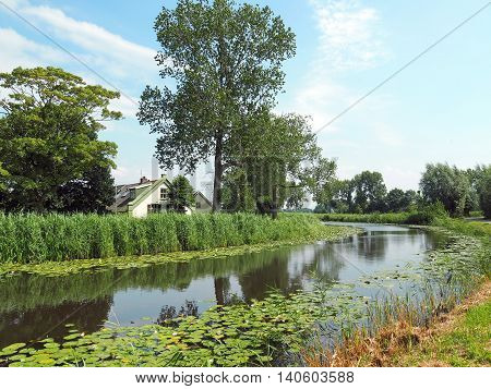 Landscape: River flows through green Low-land with Farmhouse behind the Dike