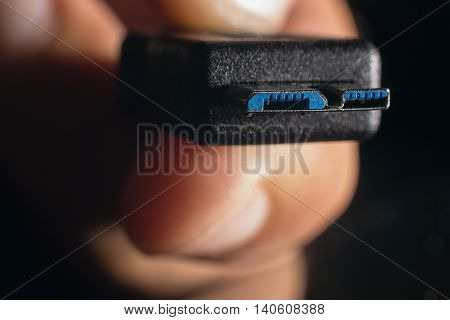 Hand holding black micro USB 3.0 cable. Man's hand holds a USB Connector. Closeup man hand holding USB cable.Selective focus and shallow Depth of field.