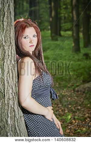 Young girl standing near a tree trunk