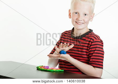 Happy Young Boy Playing With Plastic Putty