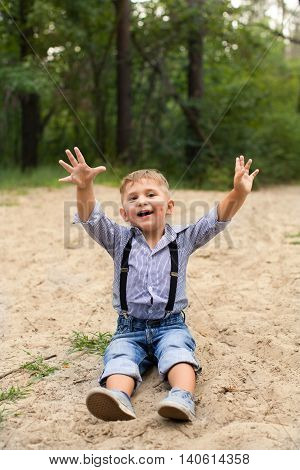 Funny boy sitting on the sand with his hands raised in a blue shirt