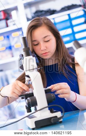 Teen school girl in biological lesson using binocular microscope with microscope slide in hand