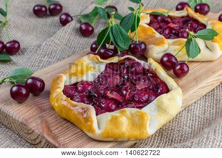 Delicious Rustical Sour Cherry Pie on Jute Fabric with a few sour cherries