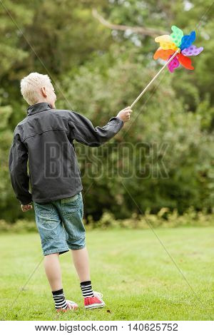Boy Wearing Black Jacket Holds Colorful Whirligig