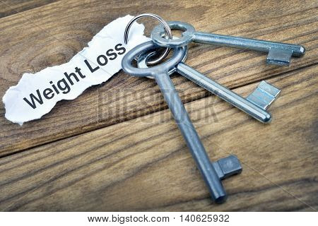 Key with message Weight Loss on wooden table