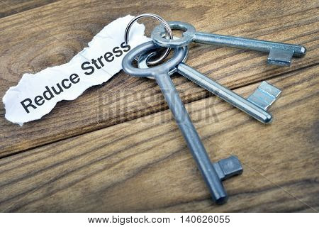 Key with message Reduce Stress on wooden table