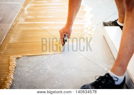 Industrial Worker Adding Glue On Cement Floor, Preparing Surface For Wood Parquet
