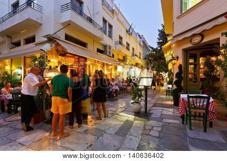 ATHENS, GREECE - JULY 29, 2016: People looking at a menu of a restaurant in Plaka on July 29, 2016.
