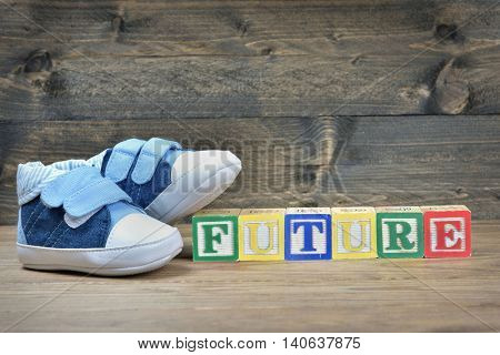Kid shoes and word future on wooden table