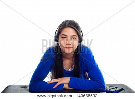Biracial Asian Caucasian teen girl in blue shirt listening to music on headphones while leaning on bench.