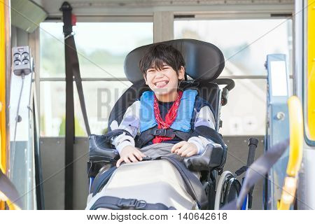 Happy biracial little boy with special needs sitting in wheelchair riding on yellow school bus lift going to school
