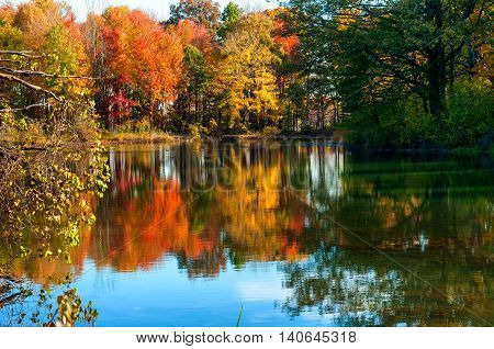 A tranquil pond reflects the colors of a late afternoon in autumn