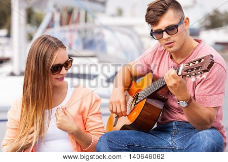 Love romance affection music sound talent concept. Girl charmed by musican. Young guitarist playing on instrument in port. poster