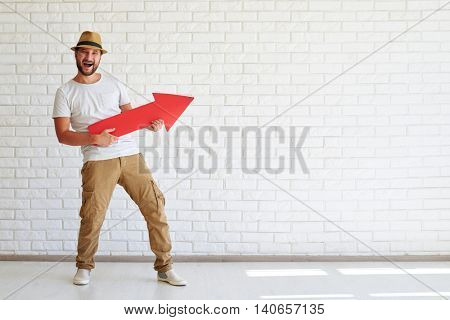 Happy keenness stylish man are standing and holding big red arrow, white brick wall in background