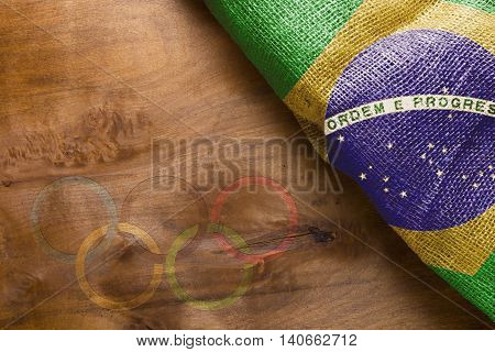 Brazilian flag and the imprint of the Olympic rings on a wooden surface.