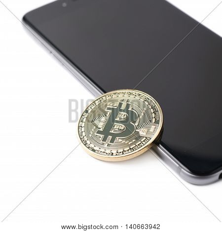 Golden bitcoin currency token over the surface of the mobile smart phone, composition isolated over the white background