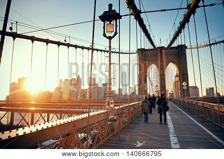 Walk on Brooklyn Bridge with pedestrians at sunset in downtown Manhattan New York City