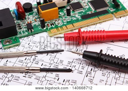 Printed circuit board with electrical components precision tools and cable of multimeter on construction drawing of electronics accessories for engineer jobs