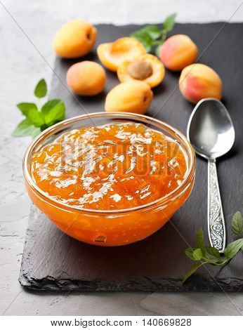 apricot jam in a glass bowl fresh apricots on black stone background