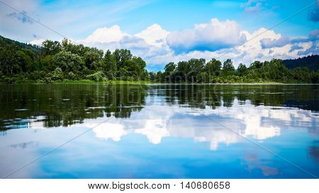 Beautiful landscape panorama with cloudy blue sky reflected in the clear water. Wooded waterside of a mountain lake. Summer idyllic beautiful landscape.