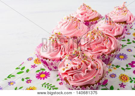 Pink cupcakes on floral napkin. Birthday cupcake with whipped cream. Homemade cupcakes served for party. Birthday background.