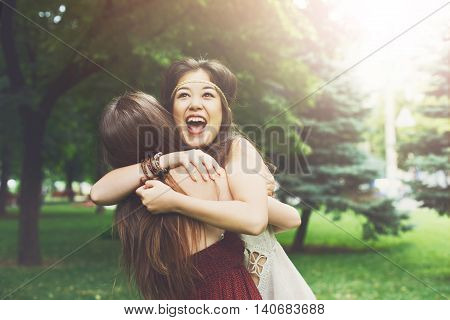 Two happy young girls hug each other. Females embracing, laughing and excited. Woman friendship, walk in the park outdoors. Asian boho girl with friend