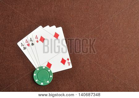 The different suit of the number 4 cards in a deck of cards displayed on a brown background with a green poker chip