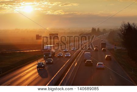 Highway transportation with cars and Truck at sunset.