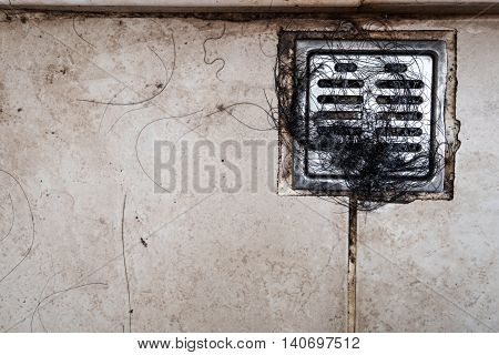Old dirty bath drain with hair clumping