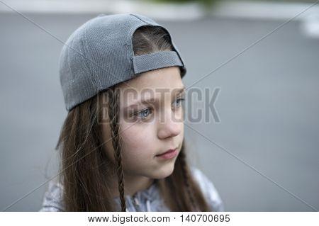 urban girl portrait in peaked grey cap in pensive mood