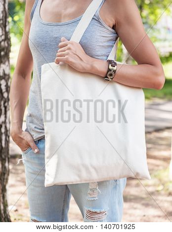Woman Holding Empty Canvas Bag. Template Mock Up