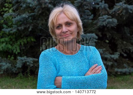 Smiling happy ellderly woman stands with crossed arms
