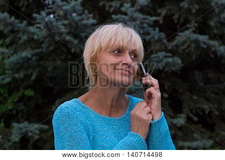 Smiling ellderly woman has a conversation by phone