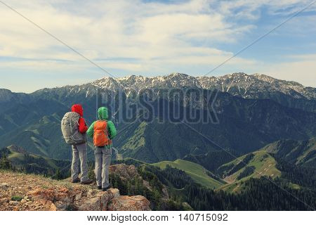 two successful women backpackers enjoy the view on mountain peak cliff