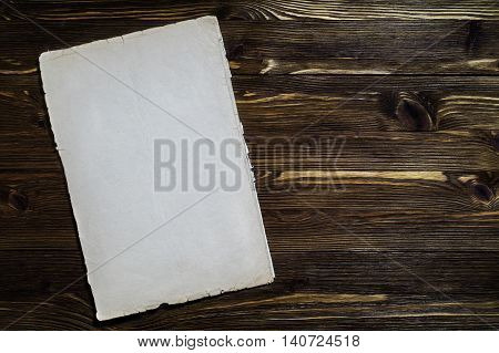 Old paper on brown aged wood. Flat lay composition. Blank Frame on Vintage Wood Background.