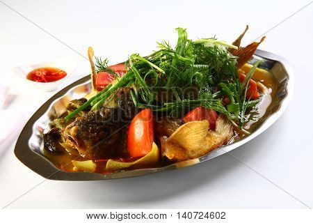 Steamed barramundi fish with onion and herbs in Hong Kong style