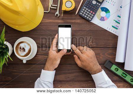 engineering using phone on his workspace top view