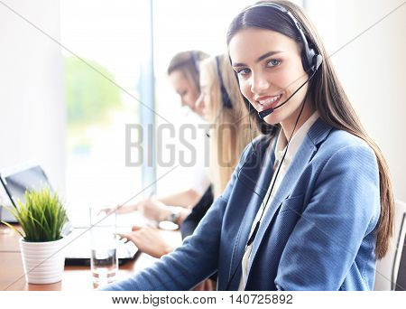 Portrait of call center worker accompanied by her team. Smiling customer support operator at work.
