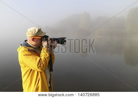 Male nature photographer in action on fogy dawn