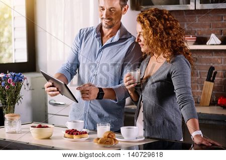 Look here. Handsome man showing a photo on the tablet to his beautiful wife who looking at it with interest while having breakfast in the morning
