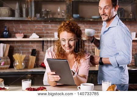 It is cant be true. Surprised woman looking at the tablet and showing it to her husband who holding a cup and opening his eyes wide