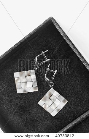 Pair of nacre earrings in black opened jewel box closeup