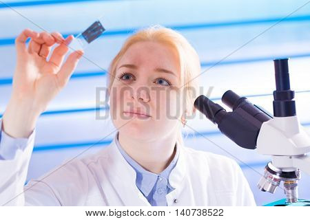 young woman with microscope slide in  laboratory