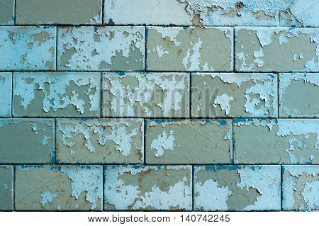 Peeling painted blue tiles on the plinth at home