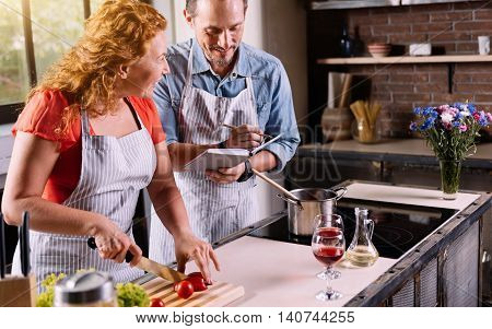 Listen carefully. Wise good looking woman dictating ingredients to her man while cutting vegetables