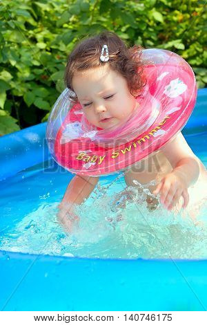 Little baby splashing in waterpool with blue water
