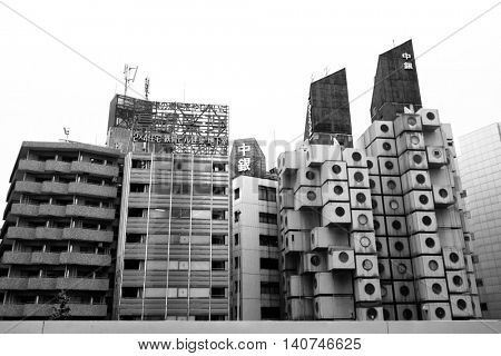 TOKYO, JAPAN - 22 JUNE 2016: The iconic Nakagin Capsule Tower in Shimbashi, Tokyo. Built in 1972 designed by Kisho Kurosawa and a rare surviving example of Japanese Metabolism style. Black and white.