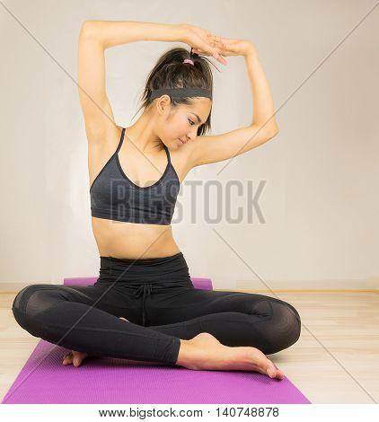 Woman sit on fitness ball after work out in gym.