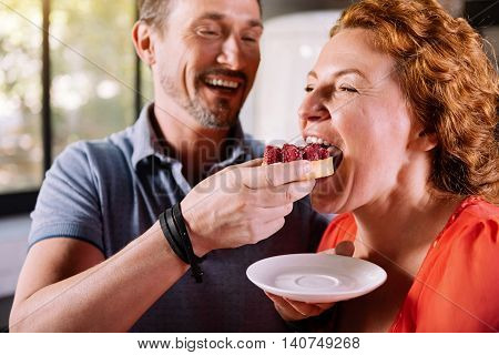 Dont think about calories . Close up of a delighted man giving to taste a new cake to his lovely beautiful woman
